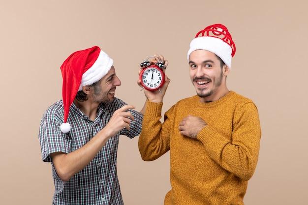Вид спереди двух счастливых мужчин, один держит будильник, а другой выключает его на бежевом изолированном фоне