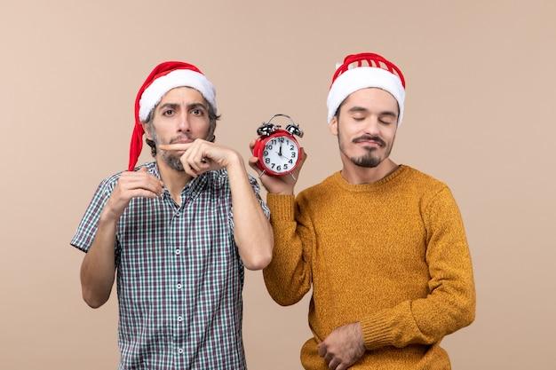 Vista frontale due uomini felici uno che fa i baffi con il dito e l'altro che tiene una sveglia con gli occhi chiusi su sfondo beige isolato