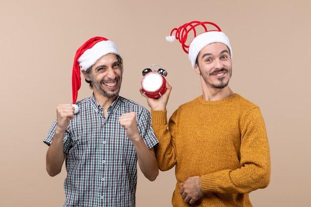 Vista frontale due uomini felici uno che fa il gesto vincente e l'altro che tiene una sveglia su fondo isolato beige