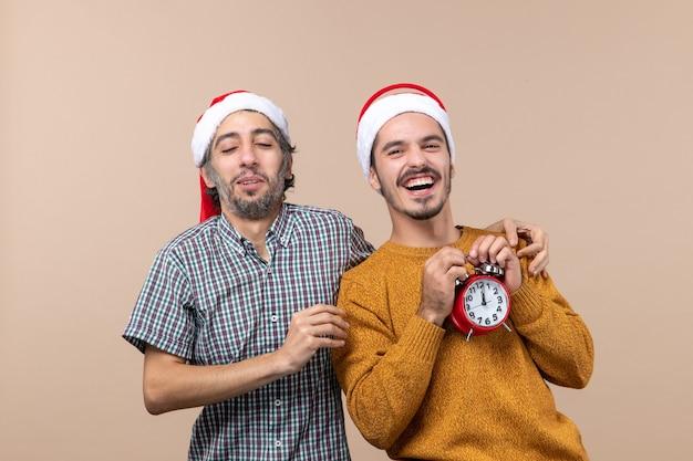 Vista frontale due uomini felici uno mettendo la mano sulla spalla di amici su sfondo beige isolato