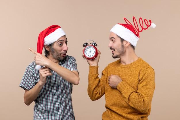 Vista frontale due uomini felici uno che mostra una sveglia a un altro su sfondo beige isolato