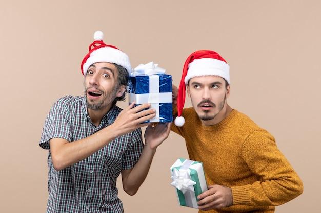Вид спереди двух заинтересованных парней в шляпах санта-клауса и обращающих внимание на рождественские подарки на бежевом изолированном фоне