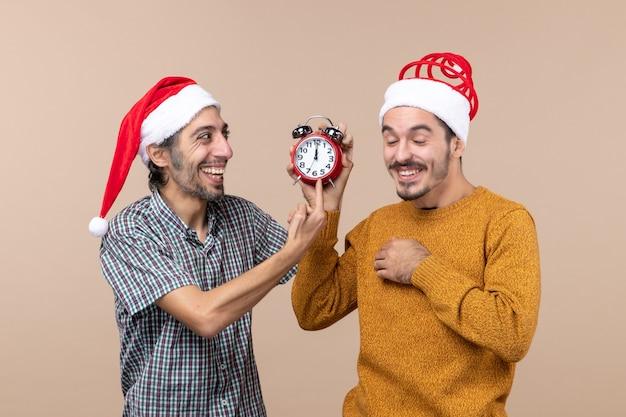 Vista frontale due uomini che ridono uno che tiene una sveglia e l'altro che mostra il tempo su fondo isolato beige