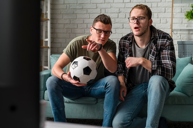 Front view of two male friends watching sports on tv together and holding football