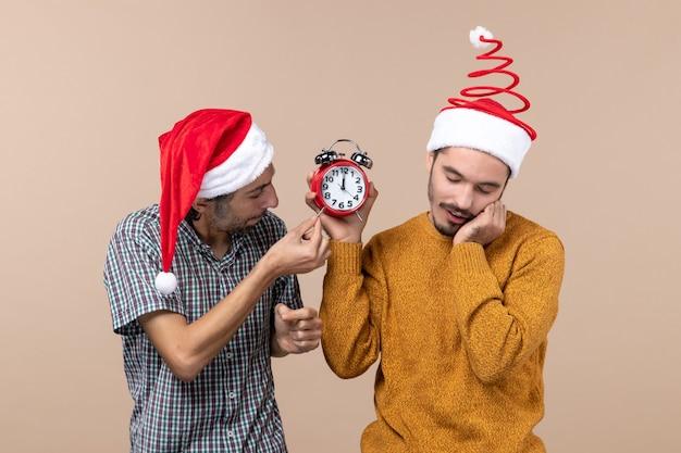 ベージュの孤立した背景に目覚まし時計を保持している2人の男性の正面図