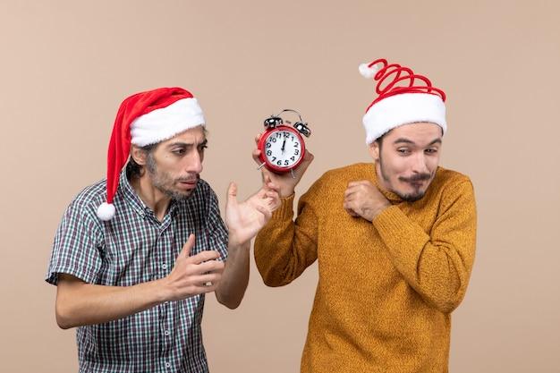 혼란스러운 두 남자와 베이지 색 격리 된 배경에 알람 시계를 들고 다른 전면보기