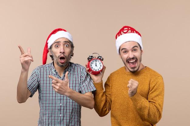 혼란스러운 두 남자와 베이지 색 격리 된 배경에 행복한 얼굴로 알람 시계를 들고 다른 남자 전면보기