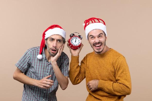 혼란스러운 두 남자와 베이지 색 격리 된 배경에 시계를 웃고있는 동안 다른 알람을 들고 전면보기