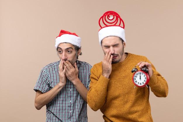 Vista frontale due uomini uno che copre la bocca con le mani e l'altro che tiene una sveglia con gli occhi chiusi su sfondo beige isolato