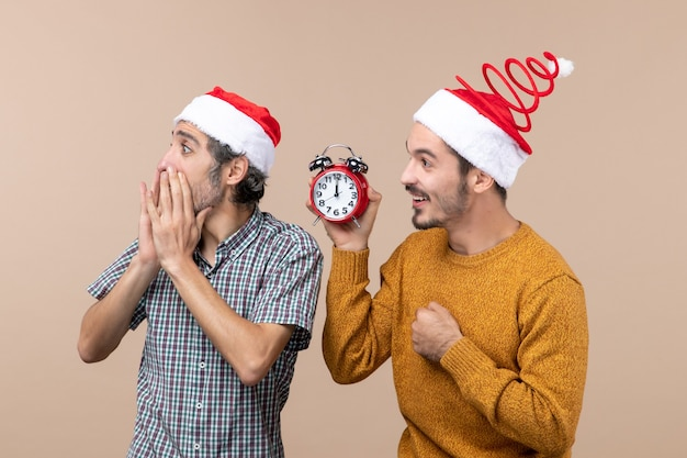 Vista frontale due uomini uno in possesso di una sveglia e l'altro chiamando qualcuno su sfondo beige isolato