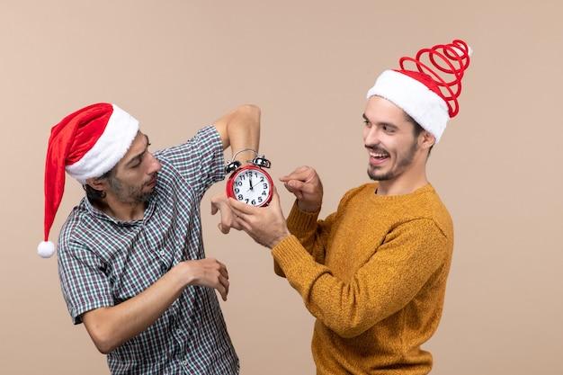 Vista frontale di due uomini uno in possesso di una sveglia e l'altro mettendola al braccio su sfondo beige isolato