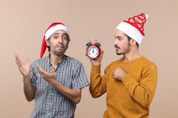 전면보기 두 남자 하나는 알람 시계를 들고 다른 베이지 색 격리 된 배경에 혼란