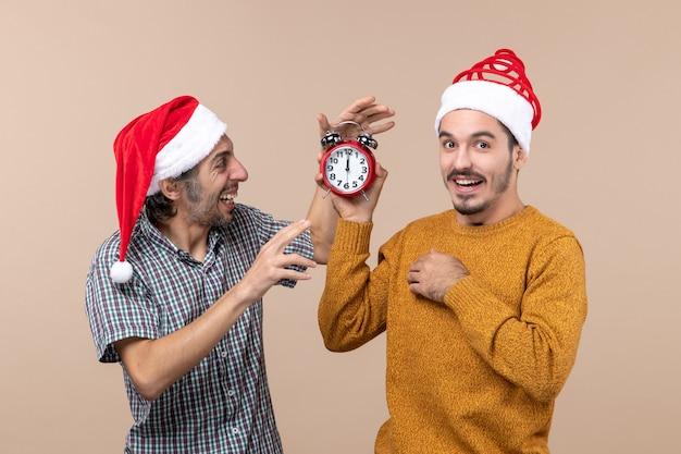 Вид спереди: двое мужчин, один держит будильник, а другой выключает его на бежевом изолированном фоне