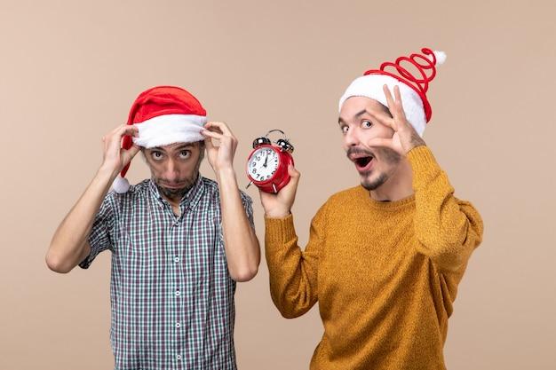 Vista frontale due uomini uno che tiene il suo cappello da babbo natale e l'altro che tiene una sveglia mentre tiene l'occhio aperto su sfondo beige isolato
