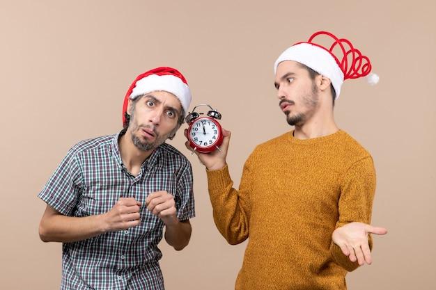 Vista frontale due uomini uno in ascolto e l'altro in possesso di una sveglia su sfondo beige isolato