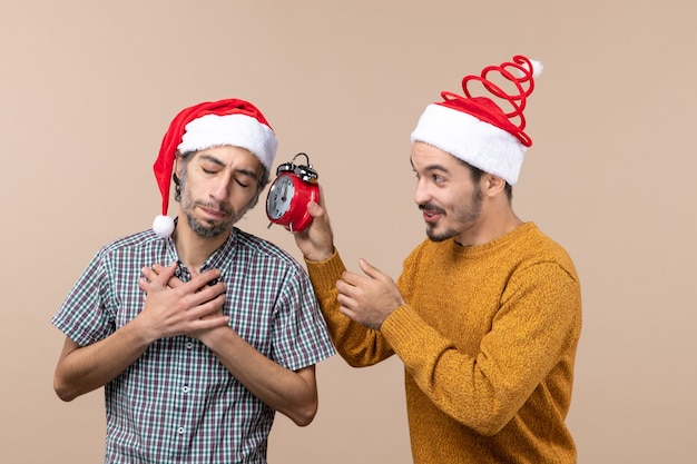 Vista frontale due uomini uno che mette le mani sul petto e l'altro che tiene una sveglia su sfondo beige isolato