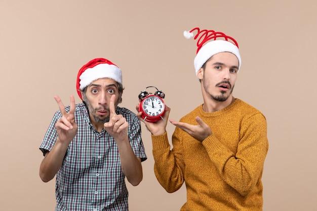 Vista frontale due uomini uno che mostra il tempo con le dita e l'altro che tiene una sveglia su fondo isolato beige