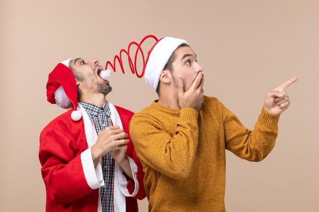 Vista frontale due uomini con cappelli di babbo natale uno che cerca di catturare cappelli pompon e l'altro che mostra la direzione su sfondo beige isolato