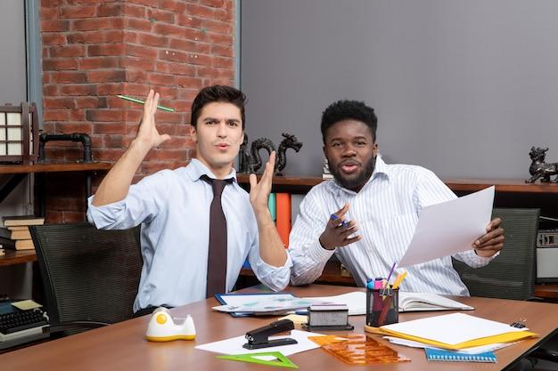 正面図2人の困惑したビジネスマン1人が紙を持っている