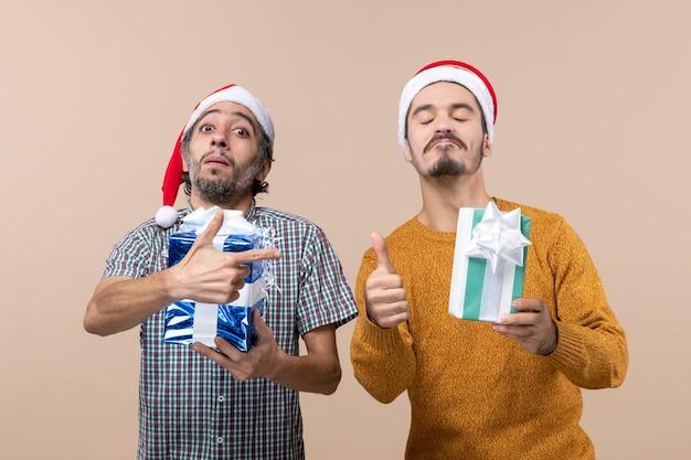 Вид спереди: двое довольных парней с подарками, один делает знак, а другой указывает на своего друга с пистолетом на бежевом изолированном фоне