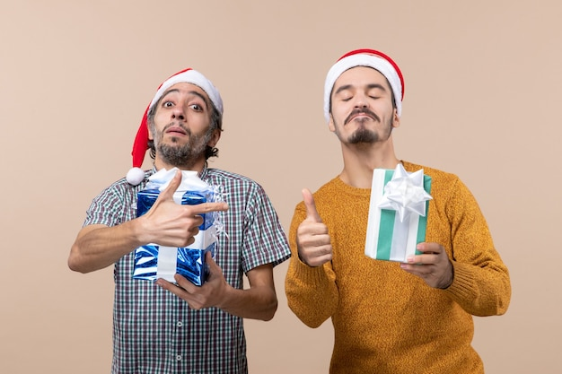 Front view two satisfied guys with presents one making thump up sign and the other pointing at his friend with finger gun on beige isolated background