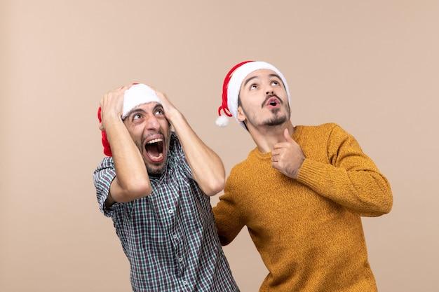 Vista frontale due ragazzi spaventati con cappelli di babbo natale guardando in alto su sfondo beige isolato