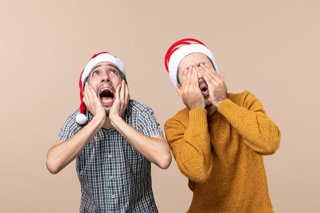 Vista frontale due ragazzi spaventati con cappelli di babbo natale uno che copre le orecchie e l'altro il viso su sfondo beige isolato