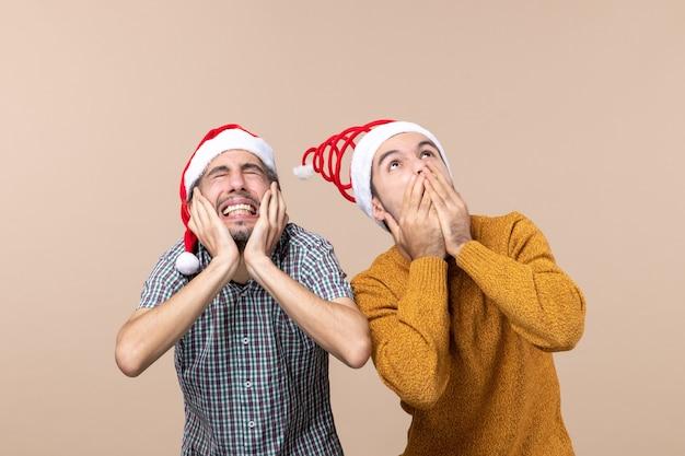 Vista frontale due ragazzi spaventati con cappelli di babbo natale uno che copre le orecchie e l'altro la bocca su sfondo beige isolato