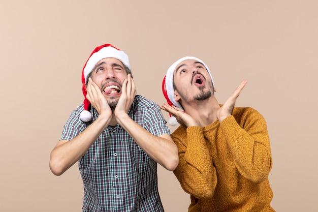 Vista frontale due ragazzi spaventati con cappelli di babbo natale uno che copre le orecchie e l'altro che grida mentre guarda in alto su sfondo beige isolato
