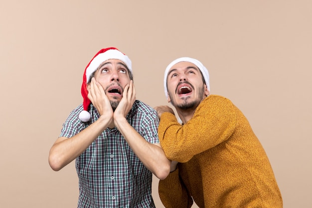 Vista frontale due ragazzi spaventati con cappelli di babbo natale uno che copre le orecchie mentre guarda in alto su sfondo beige isolato
