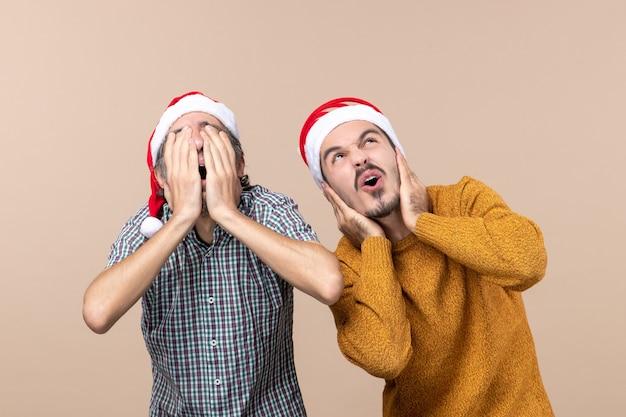Vista frontale due ragazzi spaventati con cappelli di babbo natale uno che copre il viso e l'altro le orecchie su sfondo beige isolato