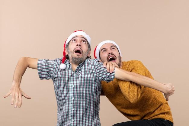 Vista frontale due ragazzi spaventati con cappelli di babbo natale uno che nasconde l'altro guardando in alto su sfondo beige isolato