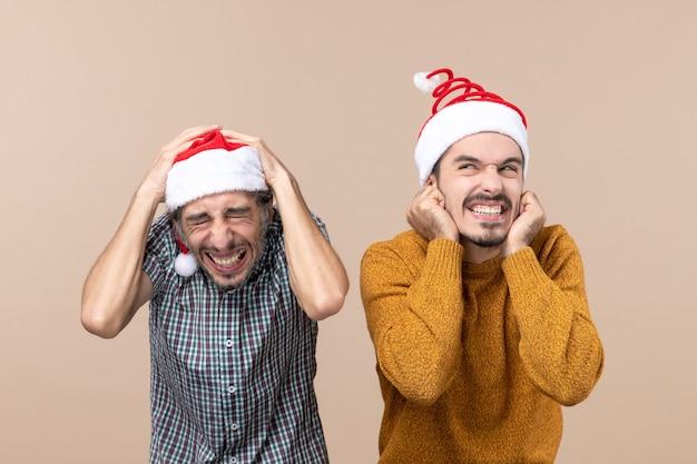 Vista frontale due ragazzi spaventati con cappelli di babbo natale uno mettendo le mani sulla testa e l'altro sulle orecchie in piedi su sfondo beige isolato
