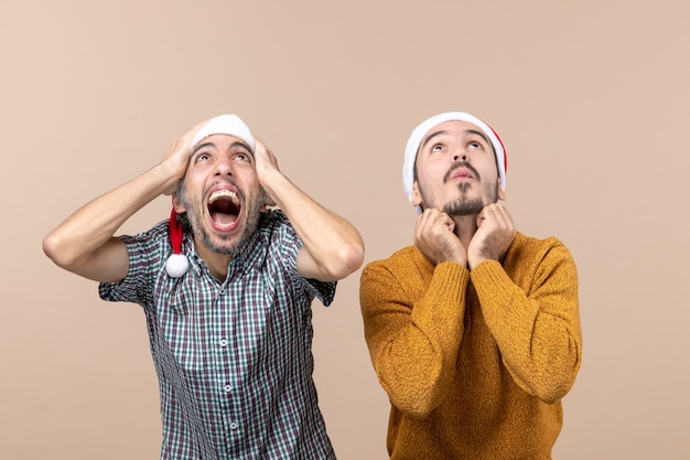 Vista frontale due ragazzi spaventati con cappelli di babbo natale uno mettendo le mani sulla sua testa l'altro sulla sua mascella in piedi su sfondo beige isolato