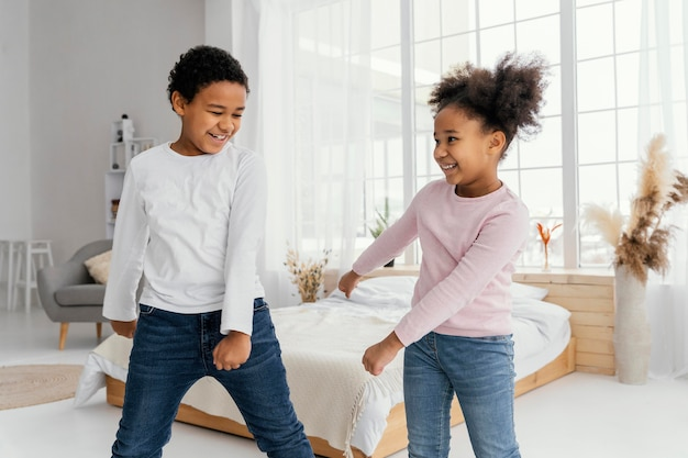 Front view of two siblings at home dancing together
