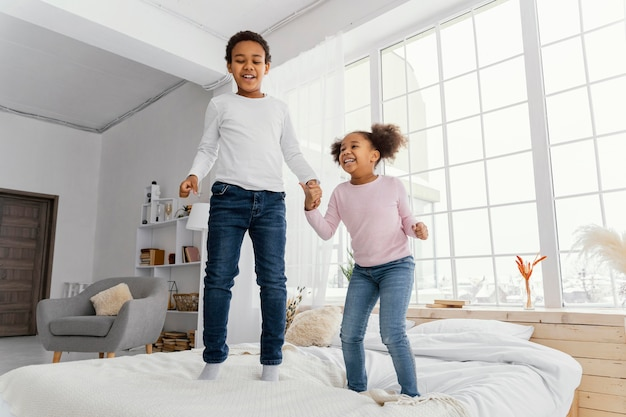 Front view of two siblings jumping in bed at home