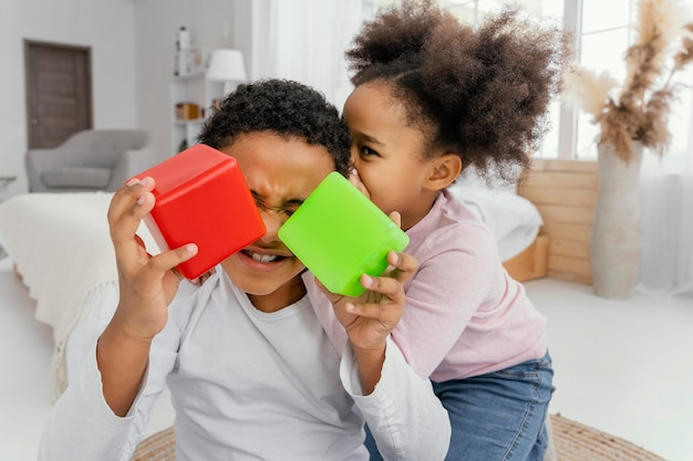Front view of two siblings playing with cubes