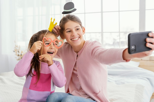Front view of two sisters at home taking selfie