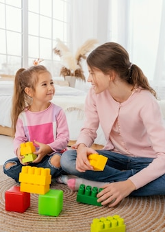 Front view of two sisters playing with toys