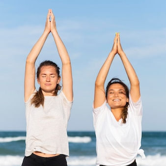 Front view of two smiley female friends working out together on the beach