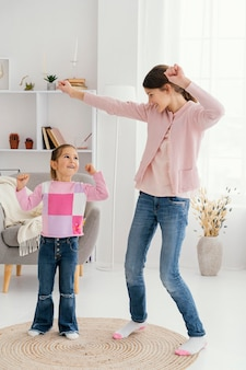 Front view of two smiley sisters dancing at home together