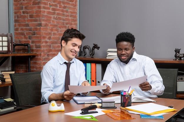 Вид спереди двух улыбающихся бизнесменов, сидящих за столом, работающих вместе в офисе