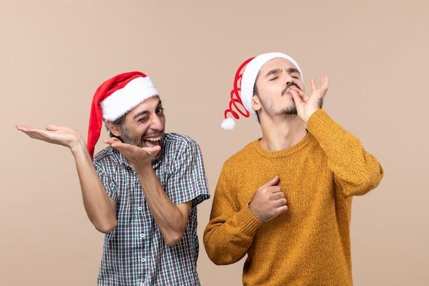 正面図サンタの帽子をかぶった2人の笑顔の男が、ベージュの孤立した背景にシェフのキスをしている