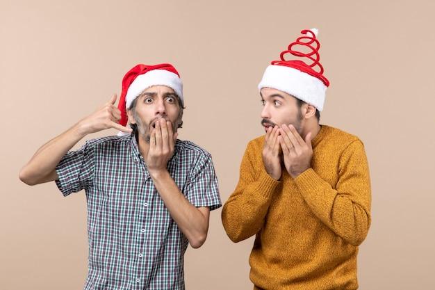 Вид спереди двух странных парней с большим удивлением в шляпах санта-клауса на бежевом изолированном фоне