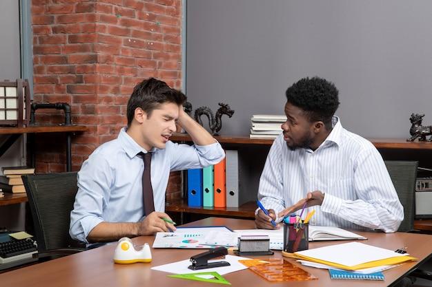 머리를 잡고 있는 동안 사무실에서 일하는 두 명의 피곤한 사업가 전면 보기