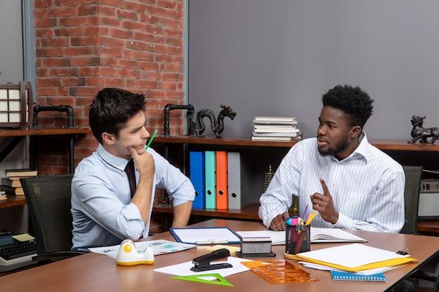 책상에 앉아 사무실에서 프로젝트에 대해 토론하는 지칠 줄 모르는 사업가 2명의 전면 보기