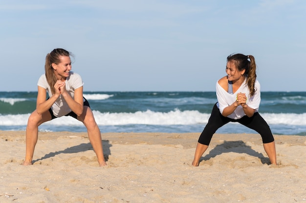 Front view of two women exercising on the beach