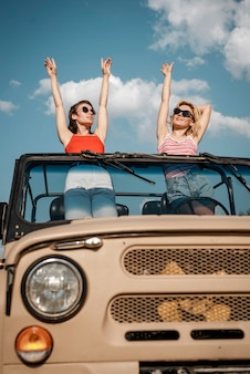 Front view of two women having fun while traveling by car