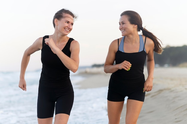 Front view of two women jogging on the beach