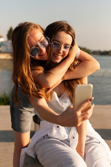 Front view of two women taking a selfie by the lake